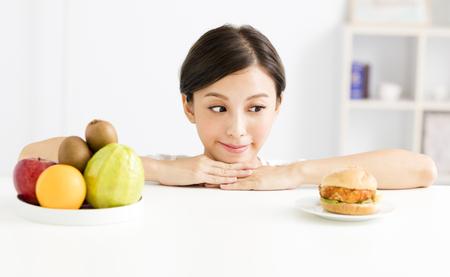 Mujer joven que elige entre alimentos saludables y nocivos