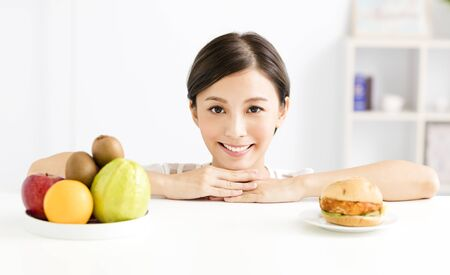 Young woman making choice between healthy and harmful food