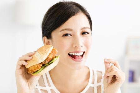 Gelukkige jonge vrouw die grote hamburger eet
