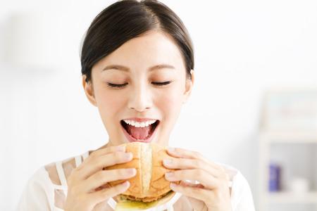 happy young  woman eating  big hamburger Stock Photo - 62779507