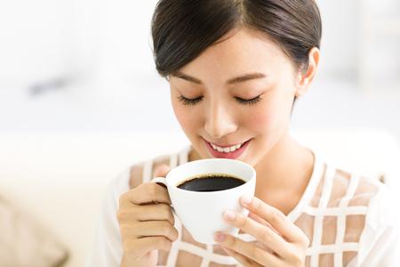 молодая улыбчивая женщина, пить кофе по утрам