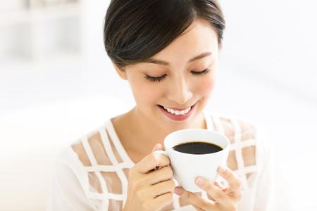 Jonge lachende vrouw drinken koffie in de ochtend