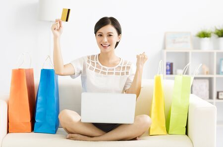 Smiling young woman shopping with laptop Imagens