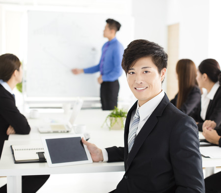 Smiling businessman looking at camera with  colleague  in meeting Stock Photo