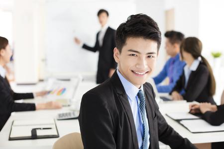 Smiling Geschäftsmann, der Kamera mit seinem Kollegen im Meeting