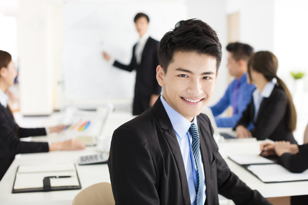 Smiling businessman looking at camera with  colleague  in meeting Foto de archivo