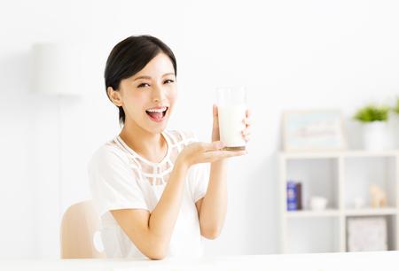 Happy young woman drinking milk Standard-Bild