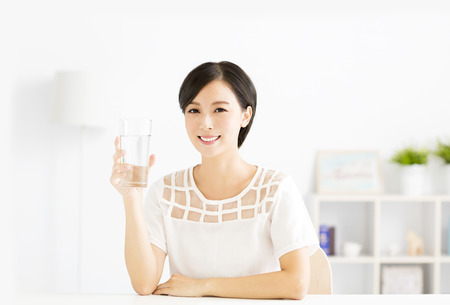 Happy young woman drinking fresh water