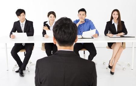 Business people interviewing young businessman in office