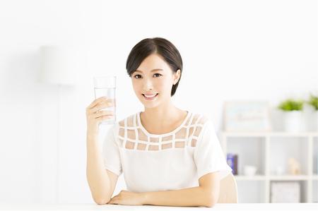Glückliche junge Frau, die trinken frisches Wasser