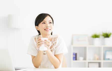 Jonge vrouw drinken koffie in de woonkamer Stockfoto