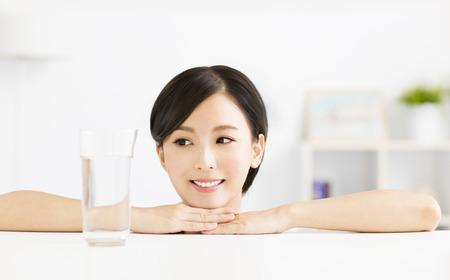 美人: 水のガラスを持つ魅力的な若い女性