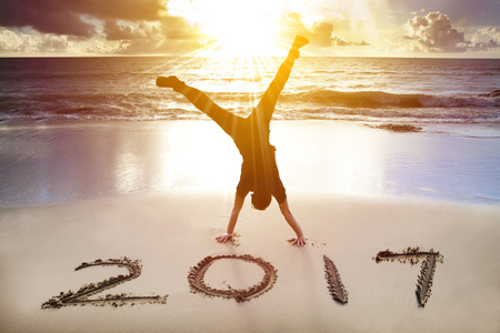 young man handstand on the beach.happy new year 2017 concept photo