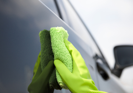 Hand  cleaning car with microfiber cloth