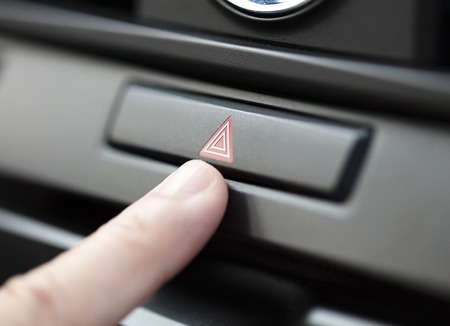 hazard: finger pressing car emergency light button