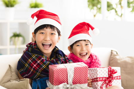 red sofa: happy little girls showing christmas gift on  sofa Stock Photo