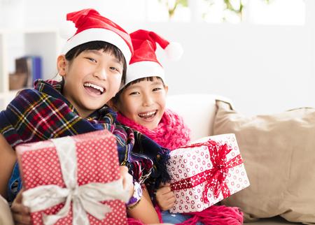 소파에 크리스마스 선물을 보여주는 행복 한 작은 소녀