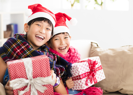 happy little girls showing christmas gift on  sofa Stock Photo