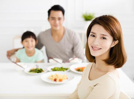 幸せなアジアの若い家族は、彼らの夕食をお楽しみください。