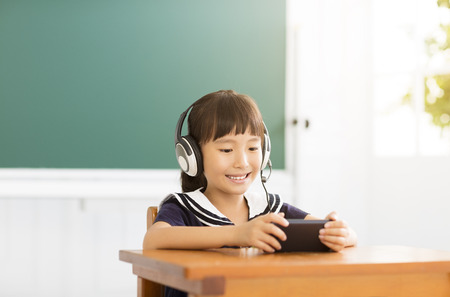 computer education: happy little girl learning with smart phone in classroom