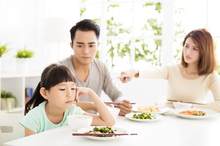 familias jovenes: niño se niega a comer mientras cena familiar