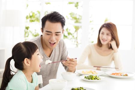 Gelukkige jonge familie genieten van hun diner
