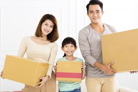 家庭: 幸福的家庭抱著箱子搬到新家
