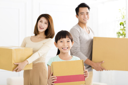 happy family holding box moving to new home Stock Photo