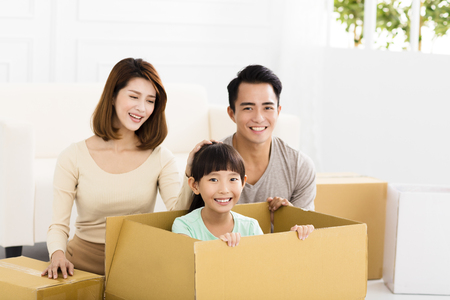 moving box: happy family holding box moving to new home Stock Photo