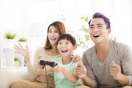 거실에서 비디오 게임을하는 가족 웃고.