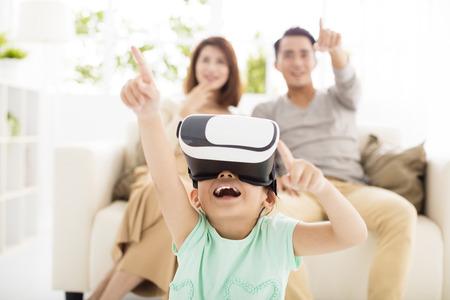 Familia feliz con casco de realidad virtual en la sala de estar Foto de archivo - 64817278