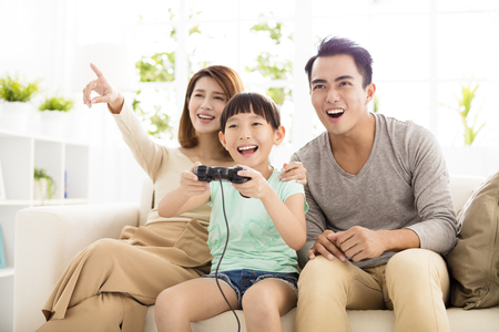 Laughing family playing video games in living room Imagens
