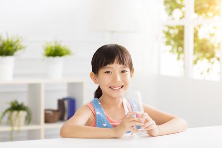 幸せな子供は、ガラスからの水を飲む 写真素材