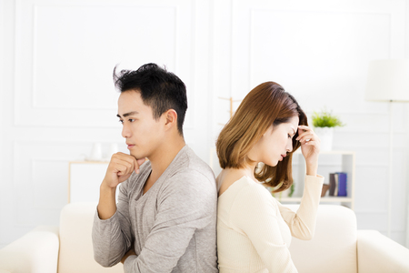 young Couple sitting back to back during conflict Stock Photo