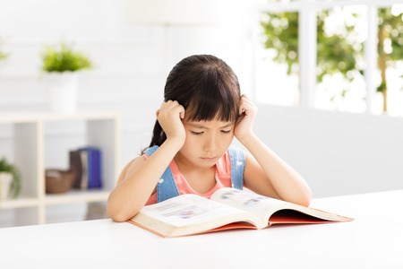 Stressed little girl study  in living room Stock Photo