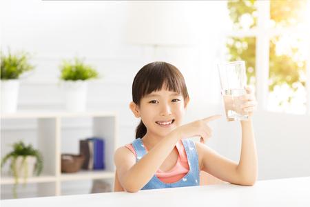 agua potable: el niño feliz bebiendo agua de vidrio Foto de archivo