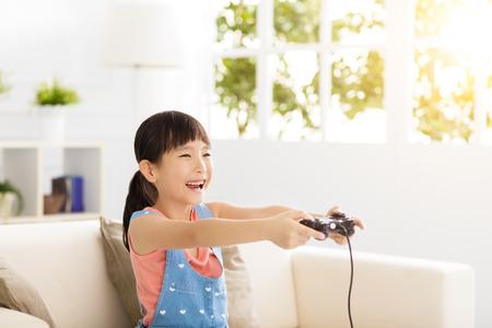 niños jugando videojuegos: Niña de risa jugando juegos de video en el sofá