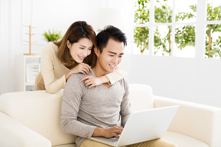 happy young couple using laptop on sofa