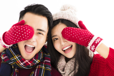 pretty face: happy couple in winter wear and covering eyes to surprised
