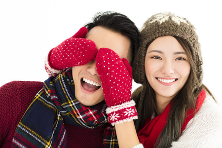 happy couple in winter wear and covering eyes to surprised