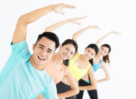 lachende jonge fit groep die zich uitstrekt in de sportschool