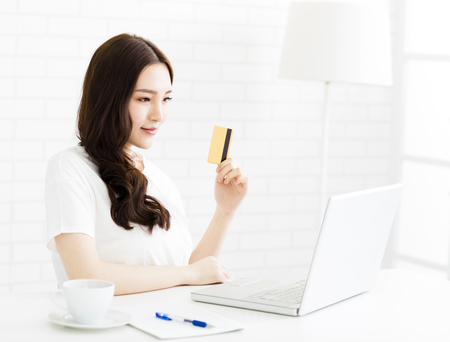 room card: happy young woman showing credit card and laptop Stock Photo