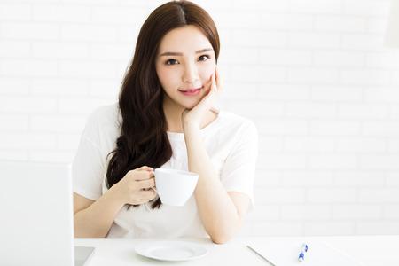 Glad ung kvinna med kaffe i vardagsrummet Stockfoto