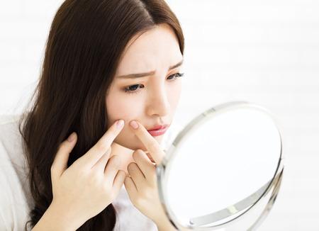 若い女性が鏡の前で彼女のにきびを絞る