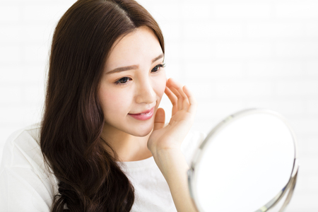 woman mirror: Happy young woman looking on mirror