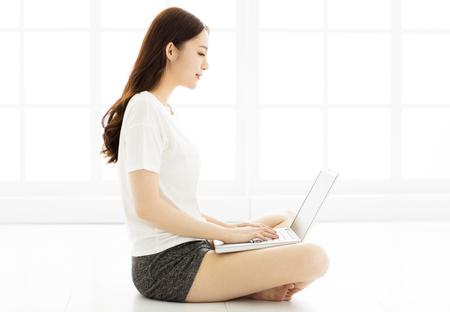 životní styl: Mladá žena sedí na podlaze s notebookem