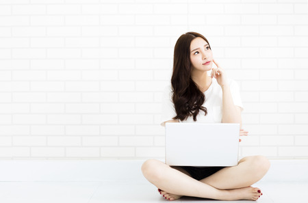niña pensando: mujer joven sentada en el suelo con el ordenador portátil Foto de archivo