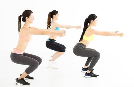 muscle training: lächelnde junge fit Gruppe Stretching und Hocke