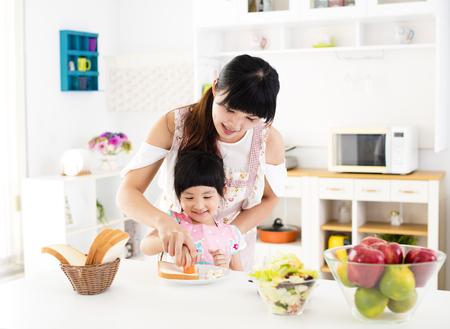 niños cocinando: niña ayudando a su madre preparar la comida en la cocina