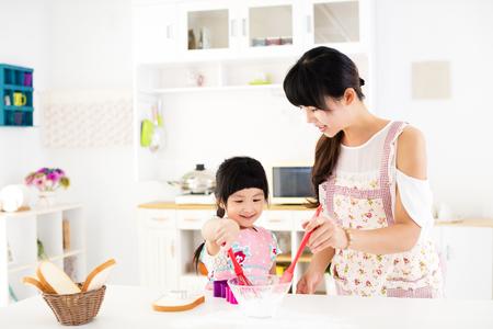 그녀의 어머니를 돕는 어린 소녀는 부엌에서 음식을 준비